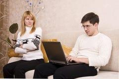 La mujer está enojada con el hombre para la computadora portátil de trabajo. Foto de archivo