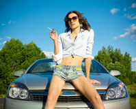 La mujer está fumando en un capo motor del coche Imagen de archivo