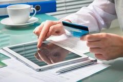 La mujer está haciendo compras en línea con PC de la tableta Fotos de archivo