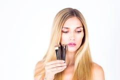 La mujer está sosteniendo cepillos cosméticos Maquillaje Foto de archivo libre de regalías
