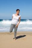 La mujer estira la pierna en la playa Imagen de archivo libre de regalías