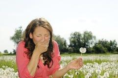 La mujer estornuda en un prado de la flor Foto de archivo libre de regalías