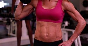 La mujer estupenda del ajuste que levanta pesas de gimnasia en rosa se divierte el sujetador metrajes