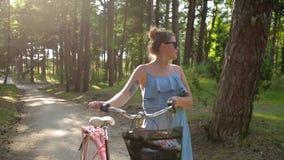 La mujer europea bonita en sundress camina y rueda la bicicleta en bosque en la puesta del sol, caminando en el aire fresco, pase almacen de metraje de vídeo