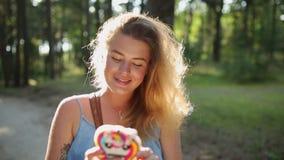 La mujer europea bonita en vestido hace el selfie y los textos con su teléfono móvil en bosque en la puesta del sol, selfie al ai metrajes