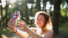 La mujer europea bonita en vestido hace el selfie y los textos con su teléfono móvil en bosque en la puesta del sol, selfie al ai almacen de video