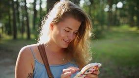 La mujer europea bonita en vestido hace el selfie y los textos con su teléfono móvil en bosque en la puesta del sol, selfie al ai almacen de metraje de vídeo