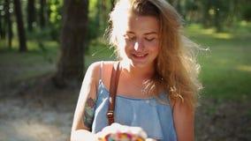 La mujer europea bonita en vestido hace el selfie y los textos con su tel?fono m?vil en bosque en la puesta del sol, selfie al ai almacen de metraje de vídeo