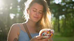 La mujer europea bonita en vestido hace el selfie y los textos con su tel?fono m?vil en bosque en la puesta del sol, selfie al ai almacen de video