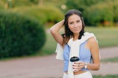 La mujer europea hermosa contenta con la figura del ajuste, guarda la mano en la cabeza, bebe el café para llevar, se opone a bac imágenes de archivo libres de regalías
