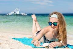 La mujer europea joven con las gafas de sol está mintiendo en la costa del mar tropical de la turquesa y wrigting por el lápiz en Fotos de archivo libres de regalías