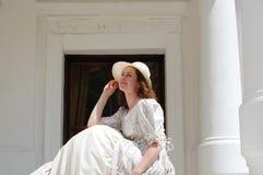 La mujer europea que se sienta en sol y el sombrero conmovedor en vintage se visten cerca de palacio Fotos de archivo