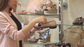 La mujer examina el zapato beige en la tienda almacen de metraje de vídeo