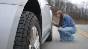 La mujer examina un plano o un neumático dañado en la parte posterior de su SUV en el camino almacen de video