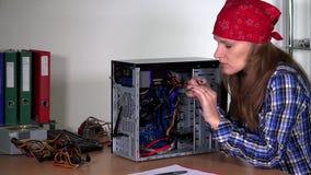 La mujer experta del trabajador del servicio informático quita y examina la placa de la memoria ram de  almacen de metraje de vídeo