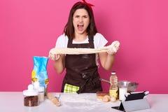La mujer expresiva emocional en cocina, hembra de grito rodeada con las herramientas para cocinar la comida, señora amasa la past fotografía de archivo