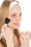 La mujer facial del adolescente del cuidado aplica el polvo con el cepillo Fotografía de archivo libre de regalías