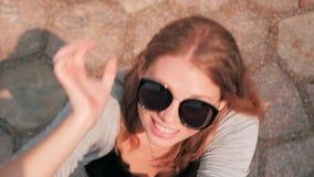 La mujer feliz alegre joven en saltos de las gafas de sol sube intentar coger la c?mara almacen de metraje de vídeo
