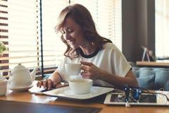 La mujer feliz atractiva caucásica leyó el mensaje de texto en su teléfono de célula Imagen de archivo libre de regalías