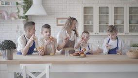 La mujer feliz atractiva del retrato y sus cuatro los hijos adolescentes que comen las empanadas y que beben el zumo de naranja e almacen de metraje de vídeo