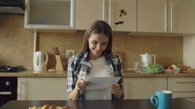 La mujer feliz atractiva recibe la letra de la lectura de las buenas noticias en la cocina mientras que tenga madrugada del desay almacen de video