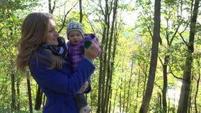 La mujer feliz con el bebé en brazos camina en parque otoñal 4K almacen de video