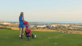 La mujer feliz con el carrito de golf viene al campo de golf almacen de video