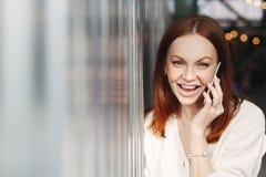 La mujer feliz con el pelo teñido, consigue buenas noticias durante la conversación sobre el teléfono celular, discute las última imagenes de archivo