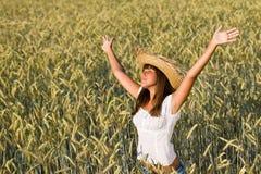 La mujer feliz con el sombrero de paja goza del sol en campo Imagen de archivo