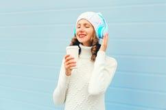 La mujer feliz con la taza de café goza escucha la música en los auriculares que llevan un sombrero hecho punto, suéter sobre azu Fotografía de archivo libre de regalías