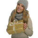La mujer feliz con los paños calientes lleva a cabo un regalo de Navidad Foto de archivo