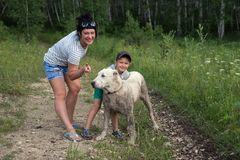 La mujer feliz con un niño y un perro blanco grande se está colocando en un camino forestal, en el verano imagenes de archivo