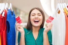 La mujer feliz con venta marca con etiqueta en la ropa en el guardarropa Imagenes de archivo