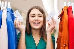 La mujer feliz con venta marca con etiqueta en la ropa en la tienda Foto de archivo