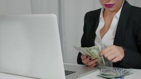 La mujer feliz cuenta dólares de EE. UU. fuera de su ordenador portátil concepto de abundancia Fotos de archivo libres de regalías