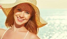 La mujer feliz de la belleza en sombrero goza del mar en la puesta del sol en la playa Imagen de archivo libre de regalías