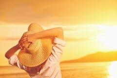 La mujer feliz de la belleza en su sombrero está detrás y admira puesta del sol sobre el mar Imagen de archivo libre de regalías