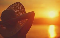 La mujer feliz de la belleza en su sombrero está detrás y admira puesta del sol sobre el mar Fotos de archivo libres de regalías