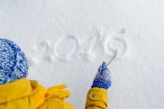 La mujer feliz de la belleza escribe un palillo en la nieve Fotos de archivo libres de regalías