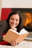 La mujer feliz de la chimenea casera leyó invierno del libro Fotografía de archivo