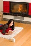 La mujer feliz de la chimenea casera leyó invierno del libro Imagen de archivo libre de regalías