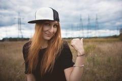 La mujer feliz de la energía joven en casquillo del hip-hop muestra los pilones del poder en el campo amarillo, cierre para arrib Imagen de archivo libre de regalías