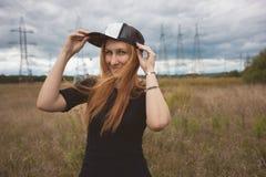 La mujer feliz de la energía joven lleva un hip-hop del casquillo en campo amarillo con los pilones del poder Foto de archivo libre de regalías