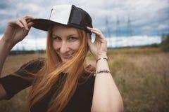 La mujer feliz de la energía joven lleva un hip-hop del casquillo en el campo amarillo con los pilones del poder, cierre para arr Fotos de archivo