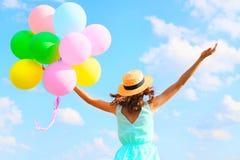 La mujer feliz de la foto de la forma de vida con los globos coloridos de un aire está disfrutando de un día de verano en fondo d Imagen de archivo