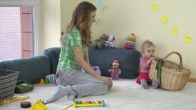La mujer feliz de la madre con la muchacha adorable de la hija del niño puso los juguetes en cesta almacen de metraje de vídeo