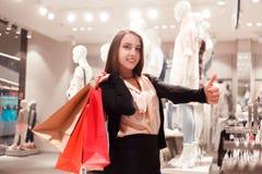 La mujer feliz de la moda con los panieres coloridos en boutique de la moda está mostrando los pulgares para arriba imágenes de archivo libres de regalías