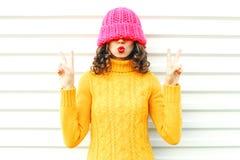 La mujer feliz de la moda que sopla los labios rojos hace beso del aire Imagen de archivo