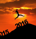 La mujer feliz de la silueta salta sobre los números 2016 Foto de archivo