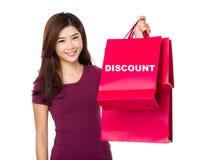La mujer feliz de las compras aumenta para arriba los bolsos que muestran un descuento de la palabra Imagen de archivo